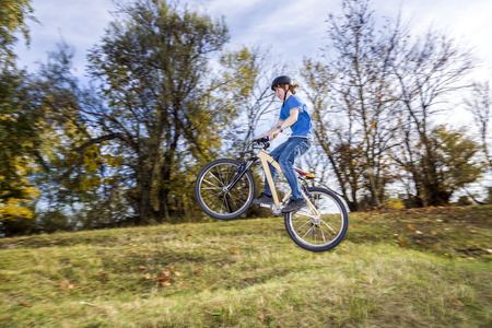 teenage boy jumps over a ramp with his dirt bike photo