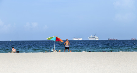 cruiseliner: MIAMI, USA - AUGUST 18, 2014: People at the sea side in Miami, USA. Miami Beach is a popular destination among tourists, spiking during the winter time.