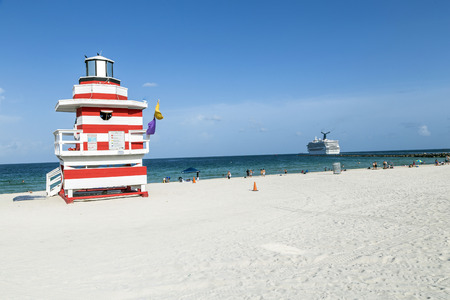 MIAMI, USA - AUGUST 18, 2014 : People enjoying the beach next to a colorful lifeguard tower in Miami, USA.