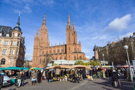 central market: Wiesbaden, Alemania - 28 de enero 2009: la gente disfruta el mercado a mercado central en Wiesbaden, Alemania. El mercado tiene lugar en frente de la iglesia del Mercado fromNew ayuntamiento a partir de 1862.