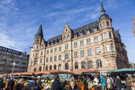 central market: Wiesbaden, Alemania - 28 de ene de 2009: la gente disfruta el mercado a mercado central en Wiesbaden, Alemania. El mercado tiene lugar en frente del Nuevo ayuntamiento desde 1883.