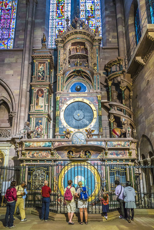 STRASBOURG, FRANCE - JULY 4, 2014: people admire the astronomical clock in the Cathedral of Strasbourg, France. It is the third clock on that spot and dates from the time of the first French possession of the city (1681–1870).