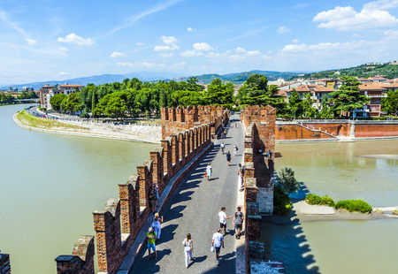 VERONA, ITALY - AUG 5, 2009: people cross the old bridge at Castelvecchio in Verona, Italy. The castle stands on the probable location of a Roman fortress outside the Roman city and was built in 1354.