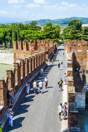 probable: VERONA, ITALY - AUG 5, 2009: people cross the old bridge at Castelvecchio in Verona, Italy. The castle stands on the probable location of a Roman fortress outside the Roman city and was built in 1354.