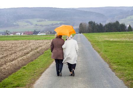 daughter in law: women in rain under an umbrella in rural landscape