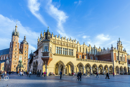 KRAKOW, POLAND - OCT 7, 2014: People on the Main Market Square near Sukiennice, Cloth Hall, and the Town Hall tower. The Cloth Hall was built in XIV century, and now hosts souvenir shops