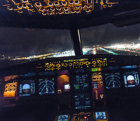 FRANKFURT, GERMANY - OCT 10, 2014: landing by night with a commercaial aircraft A320 at the airport of Frankfurt, Germany. 報道画像