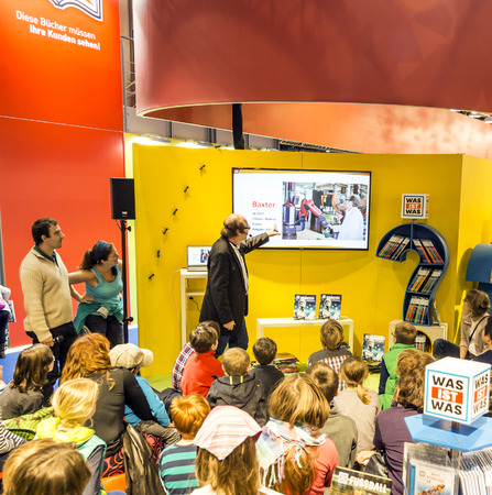 popular science: FRANKFURT, GERMANY - OCT 12, 2014: Public day at Frankfurt international Book Fair, moderator explains to children the curiosity roboter project in Frankfurt, Germany.