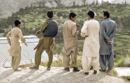pakistani pakistan: GILGIT, PAKISTAN - JUNE 30, 1987: pakistani men at Karakoram Highway in local dress watch the valley and discuss in Gilgit, Pakistan. The Karakoram Highway is the only street to china throuht wild mountain areas and valleys.