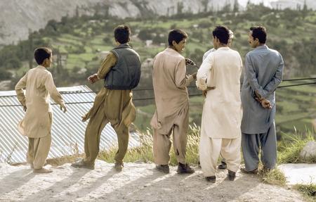 pakistani pakistan: GILGIT, PAKISTAN - JUNE 30, 1987: pakistani men at Karakoram Highway in local dress watch the valley and discuss in Gilgit, Pakistan. The Karakoram Highway is the only street to china throuht wild mountain areas and valleys.