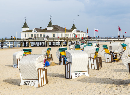 baltic people: AHLBECK, GERMANY - APRIL 20, 2014: people enjoy pier and beach of Ahlbeck, Germany. The baltic Sea in Usedom Island is famous for its unique  roofed wicker beach chairs.