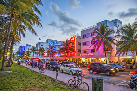 miami sunset: MIAMI, USA - AUG 23, 2014: people enjoy Palm trees and art deco hotels at Ocean Drive by night. The road is the main thoroughfare through South Beach in Miami, USA.