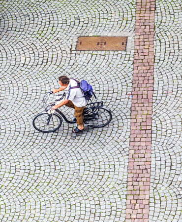 STRASBOURG, FRANCE - JULY 4, 2013: man crosses the market square at the cathedral with his bike in Strasbourg, France. The city of Strasbourg has over 18,000 bike racks and secure parking lots.