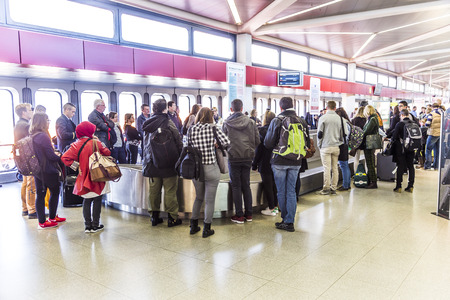 BERLIN, GERMANY - OCT 27, 2014: people wait at baggage belt  in  Tegel airport, Berlin, Germany.  It is the fourth busiest airport in Germany with . over 19.59 million passengers in 2013.