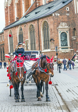 KRAKOW, POLAND - MAY 4: Horse-drawn carriage at the Market Square, standardized the color, total length of no more than 7.0 m, can be harnessed to a max of two horses on May 4, 2014 in Krakow, Poland.