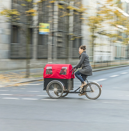 bicycle lane: BERLIN, GERMANY - OCT 29, 2014: young mother transports her child in a bicycle buggy in Berlin, Germany. Berlin has  has a good net of bicycle lanes and special signs and maps for cycling in town. Editorial