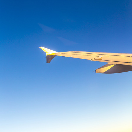 Airplane Wing in blue sky in late afternoon sun photo