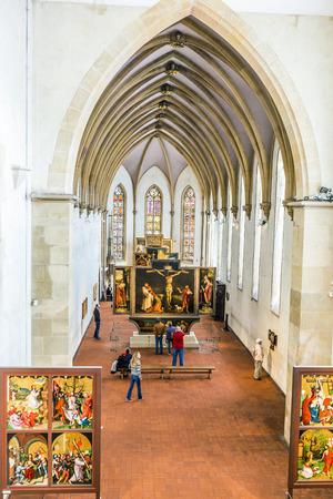 sculpted: Colmar, Frankrijk - 3 juli 2013: mensen bezoeken het Isenheimer altaarstuk, gebeeldhouwd en geschilderd door de Duitsers Niclaus van Haguenau en Matthias Grünewald in 1512-1516 in Colmar, Frankrijk. Redactioneel