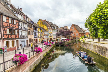 colmar: COLMAR, FRANCE - JULY 3, 2013: people visit town of Colmar, France. Colmar has thousands of small canals and therefore people call it little Venice.