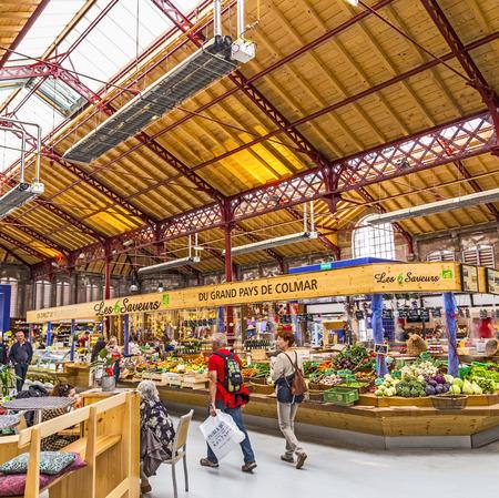 market hall: COLMAR, FRANCE - JULY 3, 2013: people shop in the old market hall in Colmar, France. Designed in 1865, this building returns to its original purpose of market hall in September 2010.