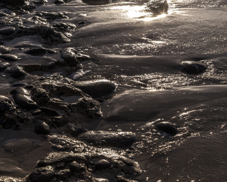 pebble stone beach in morning light with harmonic reflections photo