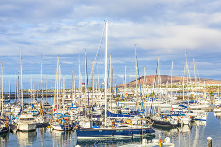 PLAYA BLANCA, SPAIN - NOV 18, 2014: Boats lie in the harbor Marina Rubicon in Playa Blanca, Spain. The Marina opened in 2003 and provides 500 berth for boats up to 70 m length.