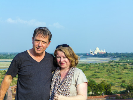 caucasian couple in love with Taj Mahal in background and blue sky photo