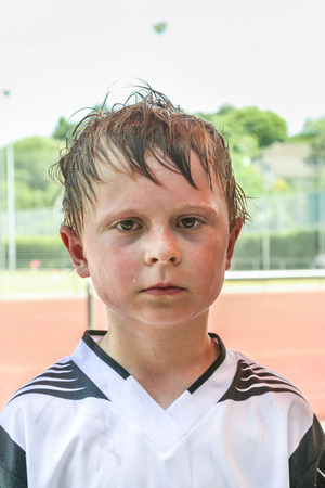boy sweating and  exhausted from playing football photo