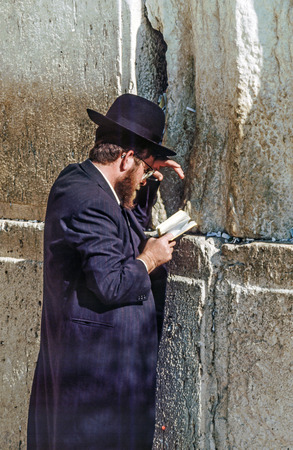 internationally: JERUSALEM - JANUARY 1 1994:  Orthodox jewish man prays at the Western Wall in Jerusalem, Israel. Israels annexation of East Jerusalem in 1967, including the Old City, was never internationally recognized.