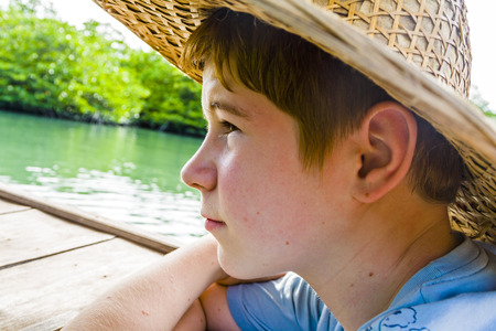 tenager: boy in a boat with straw hat in at the river in Thailand