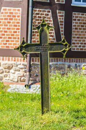 former years: OSTERHEIDE, GERMANY - APRIL 12,, 2014: old cross at the church in Osterheide, Germany. the churchyard was the cemetery in former years.