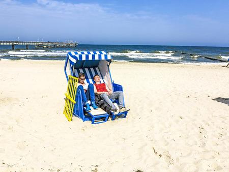 teens enjoy sunbath in the roofed wicker beach chair photo