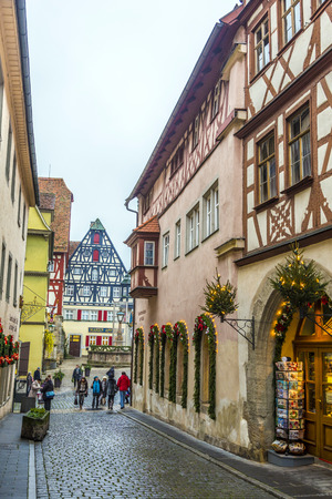 market place: ROTHENBURG, GERMANY - DEC 2, 2014: Tourists walk to the market place of Rothenburg ob der Tauber, Germany. The medieval town attracts over 2 million visitors every year. Editorial