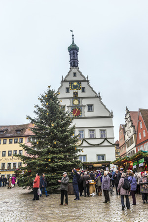 market place: ROTHENBURG, GERMANY - DEC 2, 2014: Tourists at the market place of Rothenburg ob der Tauber, Germany. The medieval town attracts over 2 million visitors every year.