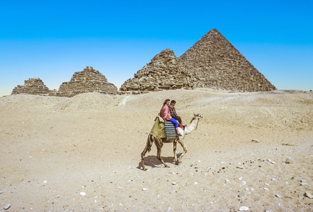cheops: GIZA, EGYPT - DEC 31, 1990: Tourists ride camel at Giza near three pyramids beginning at the smallest, the Queens Pyramids and ending at the largest, the Pyramid of Cheops.