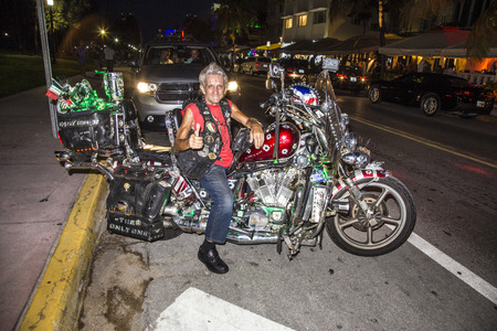 harley davidson: MIAMI, USA - AUG 193, 2014: proud Harley Davidson biker poses for a photo at Ocean Drive by night in Miami, USA. This easy rider man is a tourist attraction and loves to show thumbs up gestures.