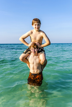warm water: brothers are enjoying the clear warm water at the beautiful beach and playing pickaback