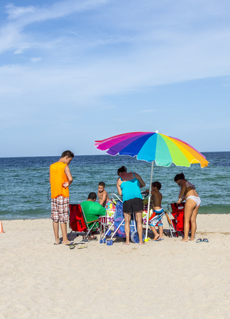 magnate: SUNNY ISLES BEACH, USA - AUG 17, 2014: people relax near the pier in Sunny Isles Beach, USA. In 1936, Milwaukee malt magnate Kurtis built the Sunny Isles beach and pier.