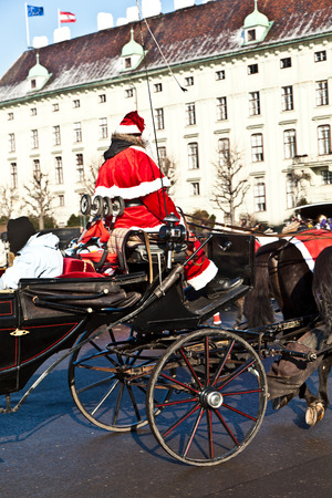 spoked: VIENNA, AUSTRIA - NOV 27, 2010: driver of the fiaker dressed as Santa Claus in Vienna, Austria. Since the 17th century, the horse-drawn carriages characterize Viennas cityscape. Editorial