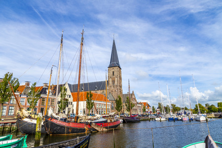 HARLINGEN, NETHERLANDS - AUG 18, 2014: pier with old boats in Harlingen, Netherlands. Harlingen became town in 1234 and is also called Venice of Netherlands. 報道画像