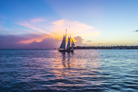florida beach: Sunset at Key West with sailing boat and bright sky Stock Photo