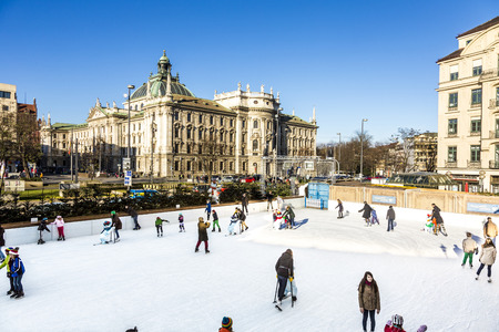 erected: MUNICH, GERMANY - DEC 24, 2014: people enjoy the Munich  EisZauber has its temporary Ice-Rink erected at Karlsplatz, Stacchus till 17th January in Munich, Germany.