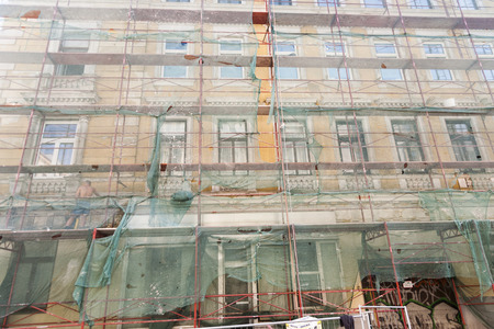 VIENNA, AUSTRIA - JULY 21, 2009: man restores facade of buildings of the 19th century in Vienna, Austria. He is protected by a net.