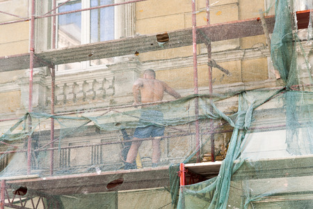 driller: VIENNA, AUSTRIA - JULY 21, 2009: man restores facade of buildings of the 19th century in Vienna, Austria. He is protected by a net.