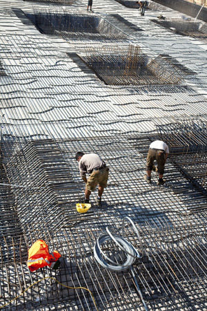 armoring: workers are doing the armoring at the building site to stabilize the fundament Editorial