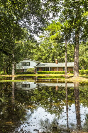 flood area: CRAWFORDVILLE, USA - JULY 24, 2013: villa in swamp area gives a harmonic mirroring picture in the water of a flood in Crawfordville, USA. Editorial