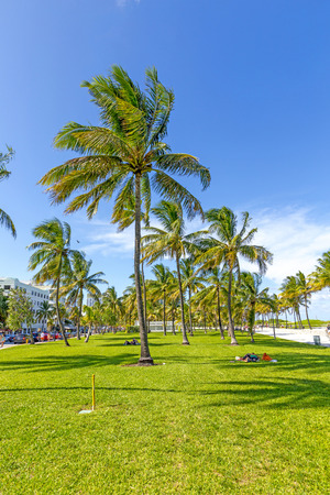 Miami, USA - AUG 1, 2013: people relaxing at beautiful Miami Beach, popular travel destination, wide angle view cityscape with palm trees and art deco architecture in Miami, USA.