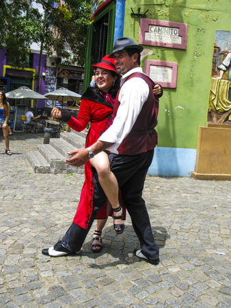 tango: BUENOS AIRES, ARGENTINA - JAN 26, 2015: tango dancer pose for tourists in Caminito Street, Buenos Aires, Argentina. Caminito is a traditional alley, located in La Boca.