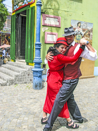 dancing house: BUENOS AIRES, ARGENTINA - JAN 26, 2015: tango dancer pose for tourists in Caminito Street, Buenos Aires, Argentina. Caminito is a traditional alley, located in La Boca.