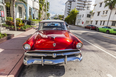 MIAMI, USA - AUG 5, 2013: The Art Deco district in Miami and a classic Ford car on Ocean Drive, South Beach, Miami, USA. Classic cars are allowed to park at yellow line.